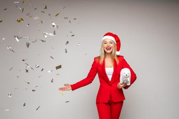 Atrakcyjna blondynka w czapce mikołaja z zabawkowym misiem, wskazując na spadającą złotą ścianę.