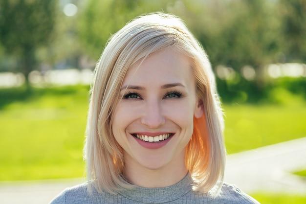 Atrakcyjna blondynka w parku na tle zielonej trawy