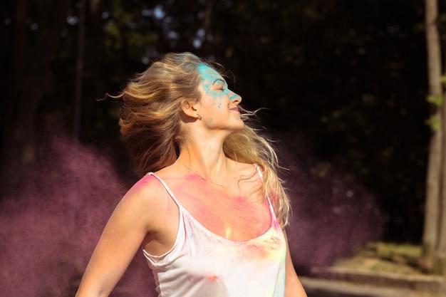 Atrakcyjna blondynka z długimi włosami powiewającymi na wietrze z różową suchą farbą holi