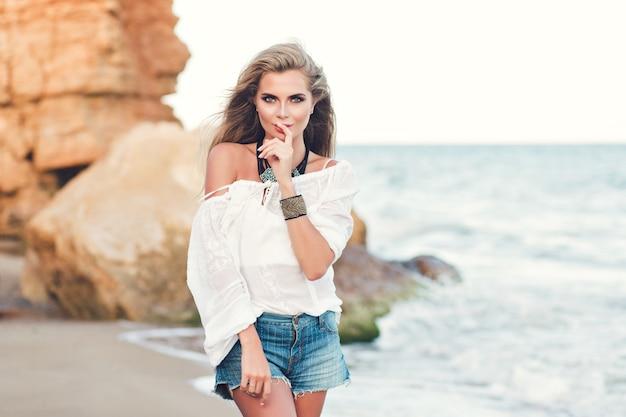 Atrakcyjna blondynka z długimi włosami pozuje na plaży w pobliżu morza. s trzyma palec na ustach i uśmiecha się do aparatu.