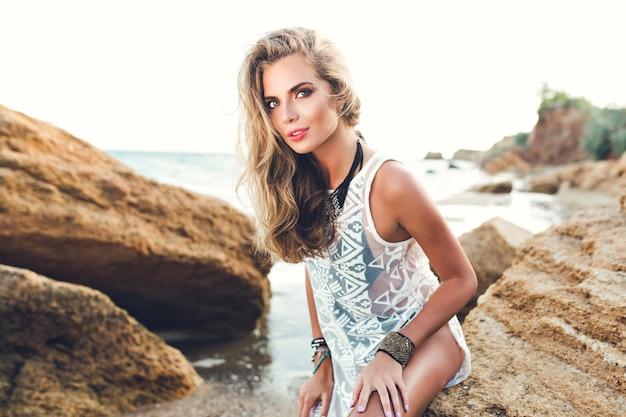 Atrakcyjna blondynka z długimi włosami siedzi na kamieniu na kamienistej plaży na tle zachodu słońca.