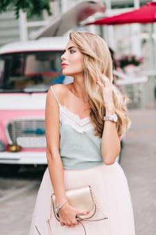Atrakcyjna blondynka z długimi włosami w tiulowej spódnicy na ulicy. trzyma włosy w dłoni, patrzy na bok.