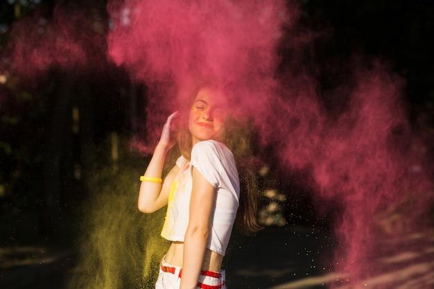 Atrakcyjna brunetka bawi się w chmurze żółtej i różowej suchej farby na festiwalu holi