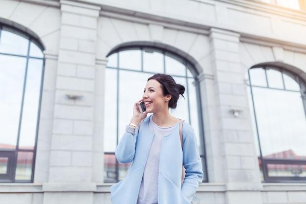 Atrakcyjna brunetka bizneswoman rozmawia przez telefon komórkowy z klientem na tle budynków biurowych