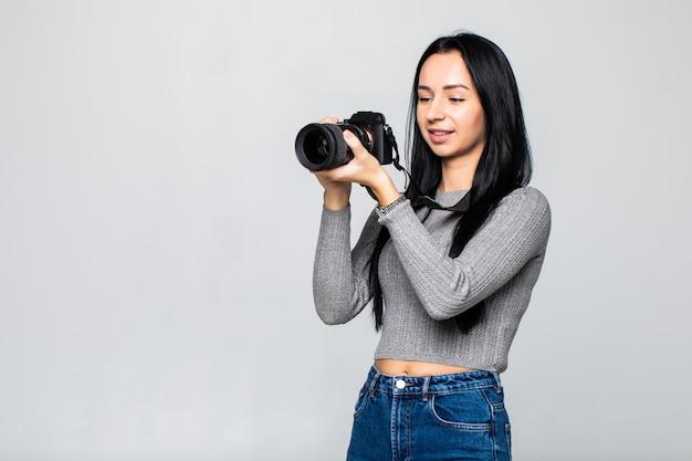 Atrakcyjna brunetka celuje w kamerę. komponowanie fotografii w studio, na szarym tle