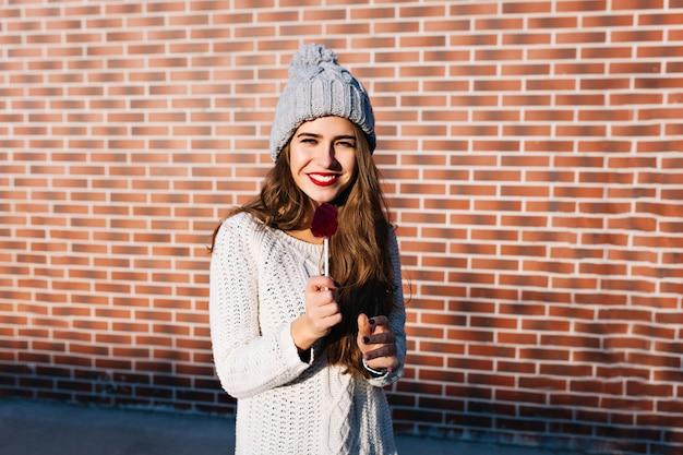 Atrakcyjna brunetka dziewczyna w biały sweter i czapka z dzianiny na ścianie na zewnątrz. śmiejąc się, trzyma czerwone usta w kształcie lizaka.