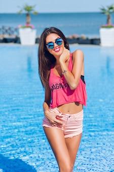 Atrakcyjna brunetka dziewczyna z długimi włosami pozuje do kamery w pobliżu basenu. trzyma ręce na ciele i uśmiecha się do kamery.
