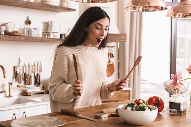 Atrakcyjna brunetka kobieta gotowanie zdrowej zielonej sałatki z warzywami w stylowej kuchni w domu