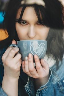 Atrakcyjna brunetka kobieta o ciemnych oczach w stylowej dżinsowej kurtce pije z niebieskiego kubka z nadrukiem gorącego napoju serca i pewnie patrzy w kamerę