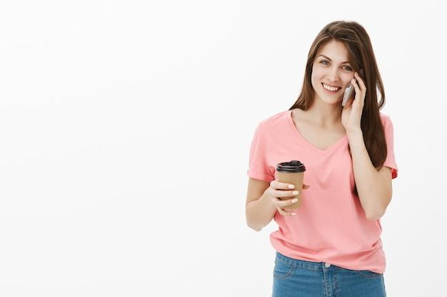Atrakcyjna brunetka kobieta pozuje w studio z jej telefonem i kawą