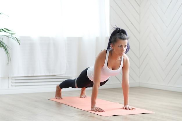 Atrakcyjna brunetka kobieta robi joga w domu.