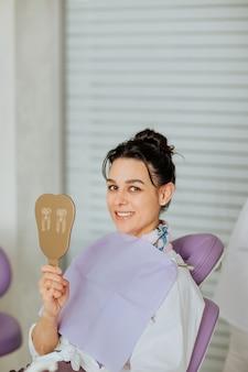 Atrakcyjna brunetka kobieta trzyma lusterko dentystyczne i siedzi na fotelu lekarskim w klinice