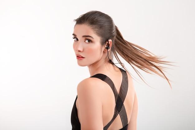 Atrakcyjna brunetka kobieta w czarny top joggingu słuchanie muzyki na słuchawkach pozowanie na białym tle na białym tle fryzura w kucyk macha długimi włosami
