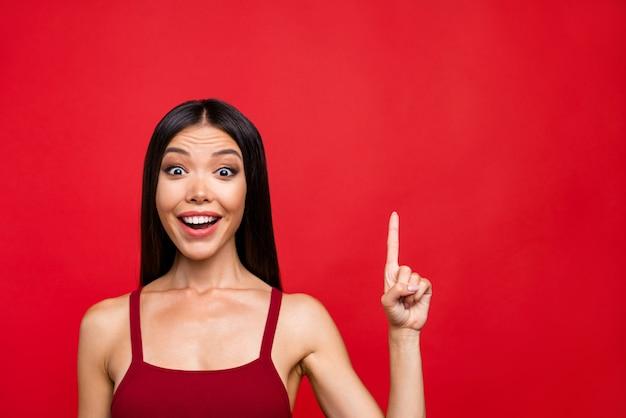 Atrakcyjna brunetka kobieta w czerwonej sukience pozuje na czerwonej ścianie