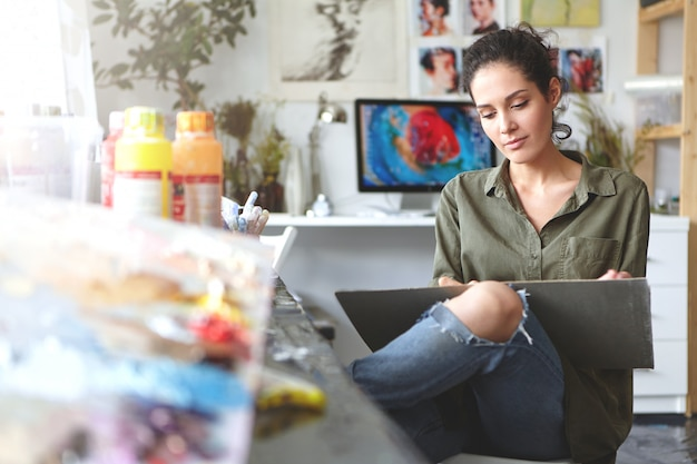 Atrakcyjna brunetka młoda europejska artystka wyrażająca swoje pomysły poprzez malowanie, szczęśliwa z zawodu, ciesząca się procesem tworzenia czegoś nowego. sztuka, rzemiosło i kreatywność