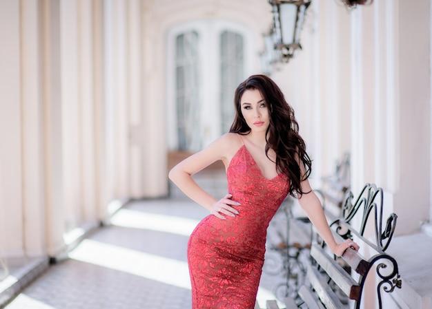 Atrakcyjna brunetka, młoda kaukaska kobieta z idealnym ciałem w słoneczny dzień w pobliżu budynku opiera się na ławce