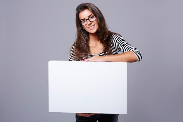 Atrakcyjna brunetka niosąca poziomą tabliczkę