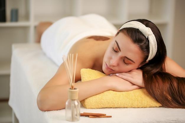 Atrakcyjna brunetka relaksująca się z zamkniętymi oczami i korzystająca z zabiegów spa.