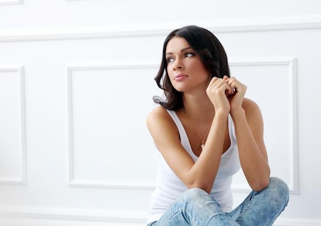 Atrakcyjna brunetka siedzi na podłodze