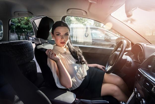 Atrakcyjna brunetka siedzi w samochodzie i pokazuje klucz