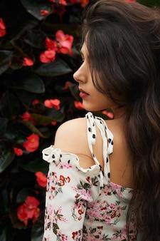 Atrakcyjna brunetka w ślicznej sukience w pobliżu kwiatów