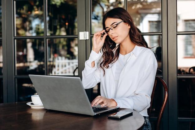 Atrakcyjna brunetka w szkłach pracuje na laptopie na nowym projekcie