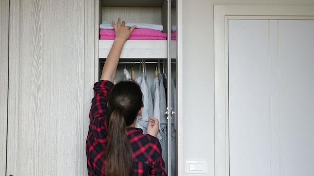 Atrakcyjna brunetka z kucykiem bierze biały miękki ręcznik kąpielowy z półki w szafie i odchodzi z pokoju w domu