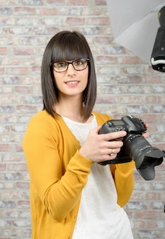 Atrakcyjna brunetki kobieta z fotografii kamerą w studiu