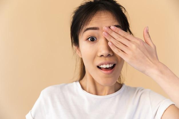 Atrakcyjna chińska kobieta ubrana w podstawową koszulkę zakrywającą oczy i zerkającą na beżową ścianę w studio