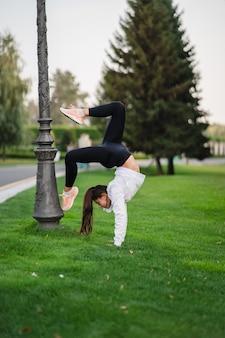 Atrakcyjna chuda kobieta robi wygięcie do tyłu, pokazując salto.