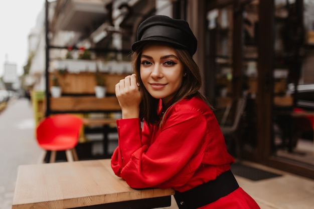 Atrakcyjna ciemnowłosa dziewczyna o głębokim spojrzeniu i wspaniałych brwiach pozuje do portretu z bliska przeciwko ulicznej kawiarni