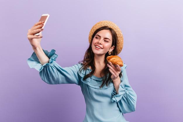 Atrakcyjna ciemnowłosa dziewczyna trzyma rogalika i robi selfie na liliowej ścianie.