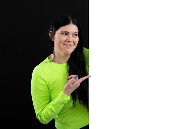 Atrakcyjna ciemnowłosa kobieta w jasnych kolorowych ubraniach z białym pustym plakatem, na białym tle na ciemnym tle