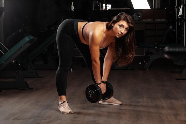Atrakcyjna curvy młoda kobieta pracująca z dumbbell w gym out, ciemny tło