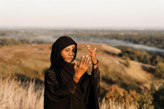 Atrakcyjna czarna kobieta modli się do allaha w jego modlitwie w miesiącu ramadan.