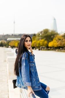 Atrakcyjna czarnowłosa dziewczyna pozuje na tle nowoczesnej architektury miasta baku