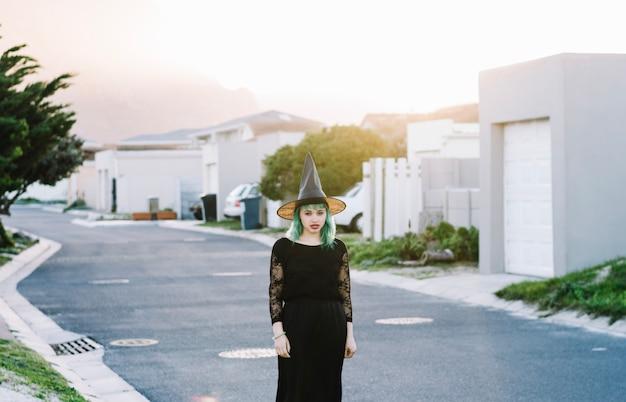 Atrakcyjna czarownica stojąca na ulicy