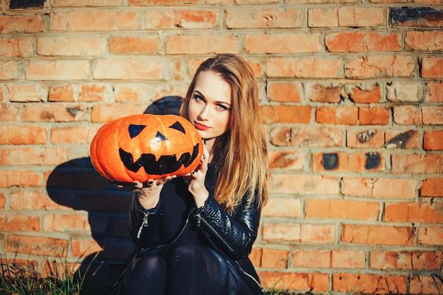 """Atrakcyjna czarownica trzymająca dyniową """"cukierek albo psikus""""."""