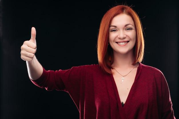 Atrakcyjna czerwona z włosami dziewczyny mienia ręka z kciukiem up.
