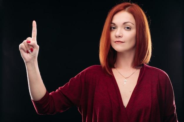 Atrakcyjna czerwona z włosami dziewczyny mienia ręka z palcem up.