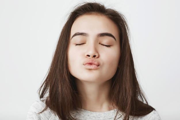 Atrakcyjna czuła kobieta europejska czekająca na pocałunek z założonymi ustami i zamkniętymi oczami.