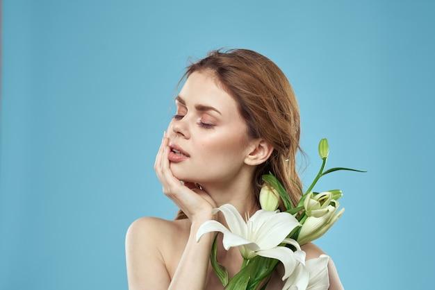 Atrakcyjna dama białe kwiaty niebieskie tło portret przycięty widok