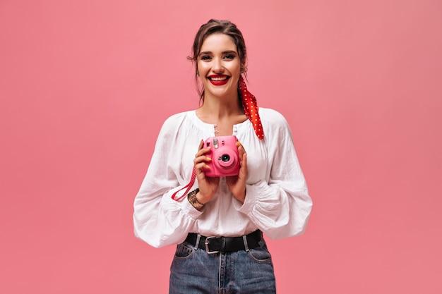 Atrakcyjna dama pozuje z różowym aparatem. piękna kobieta z czerwonym bandażem na głowie i jasną szminką, uśmiechając się.