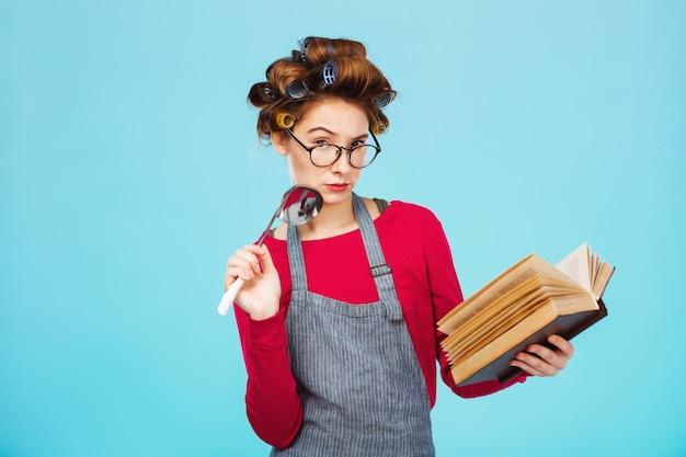 Atrakcyjna dama szuka nowego przepisu, trzymając w rękach kadzi zupę