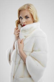 Atrakcyjna dama w białym futerkowym żakiecie