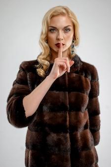 Atrakcyjna dama w brown futerkowym żakiecie. idealny makijaż, czerwone matowe usta i niebieskie oczy.