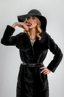 Atrakcyjna dama w czarnym futerkowym żakiecie i kapeluszu. idealny makijaż, czerwone matowe usta i niebieskie oczy.