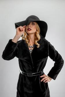 Atrakcyjna dama w czarnym futrze i kapeluszu.