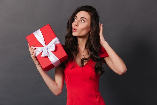 Atrakcyjna dama w eleganckiej jasnej sukience wygląda na zaskoczoną z boku i trzyma czerwone pudełko z białą kokardką.