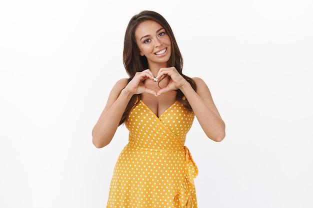 Atrakcyjna delikatna kobieca młoda kaukaska kobieta w żółtej letniej sukience, przechyla głowę i głupio uśmiecha się, pokazuje znak serca, wyznaje miłość i uczucie, wykonując romantyczny zalotny gest, biała ściana